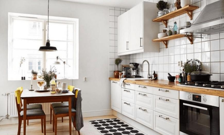 белая кухня с деревянной столешницей в интерьере